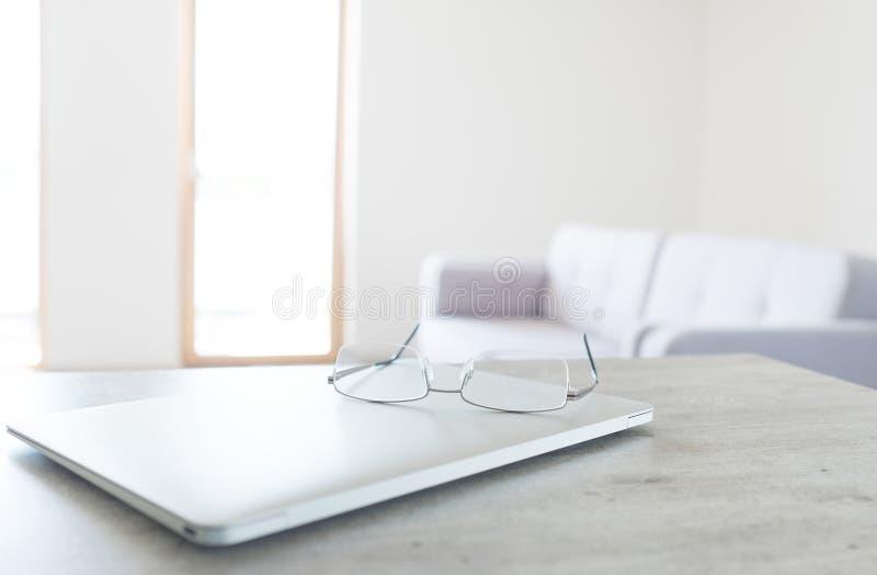 Mening die van glazen op moderne laptop met Skandinavisch ontwerpbinnenland liggen stock foto