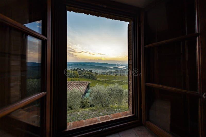 Mening door een venster aan een zonsopgang over mistige heuvels in Toscanië royalty-vrije stock foto