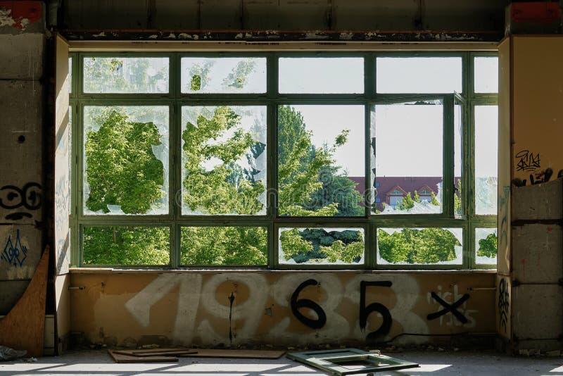 Mening door een venster in een verlaten fabriek royalty-vrije stock afbeelding