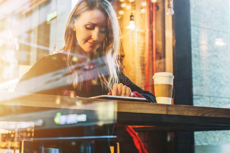 Mening door glas Jonge het glimlachen bedrijfsvrouwenzitting in koffie bij lijst, het drinken koffie en het gebruiken van tabletc royalty-vrije stock foto's