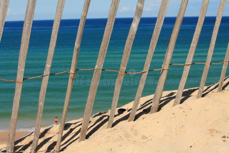 Mening door houten omheining in hete de zomerdag op de Atlantische Oceaan stock afbeeldingen