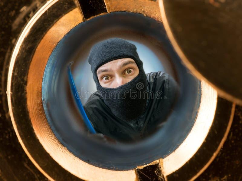 Mening door kijkglas Rover of inbreker met balaclava achter deur wordt gemaskeerd die stock afbeelding