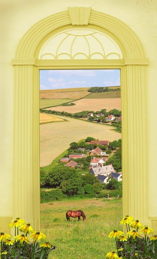 Mening door overspannen deur, heuvelig landschap en weinig dorp stock afbeelding