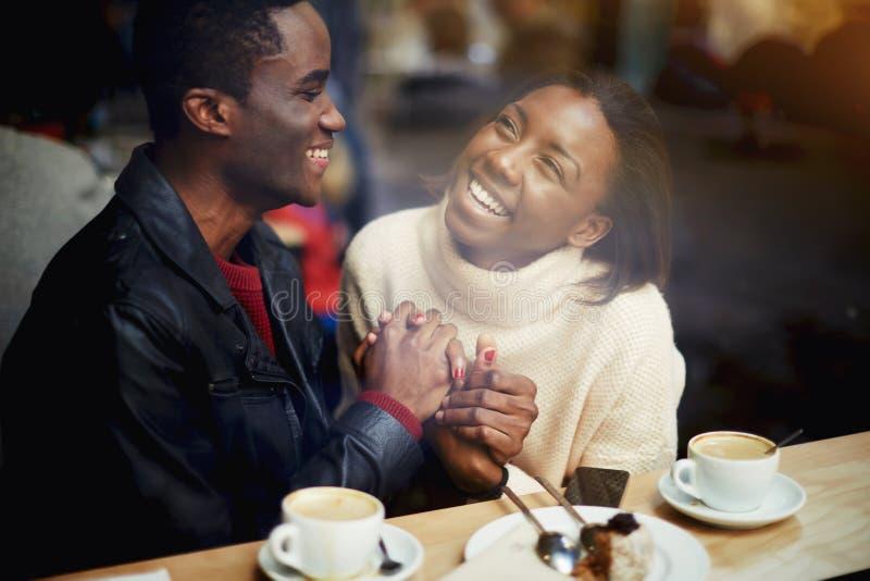 Mening door venster van vrolijke gelukkige minnaars die van vrije tijd genieten terwijl het zitten in bar in koude de winterdag, stock foto's