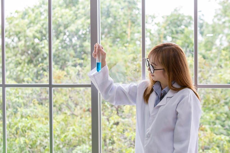 Mening för ande för vetenskapswhitblått Vetenskapliga viktblått in på hennes hand på labbet en bakgrund Härlig le kvinnlig doktor royaltyfri bild