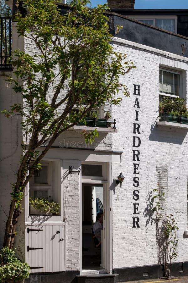 Mening onderaan een originele miauwenzijstraat in Kensington, Londen die UK, witte geschilderde gebouwen het tonen royalty-vrije stock fotografie