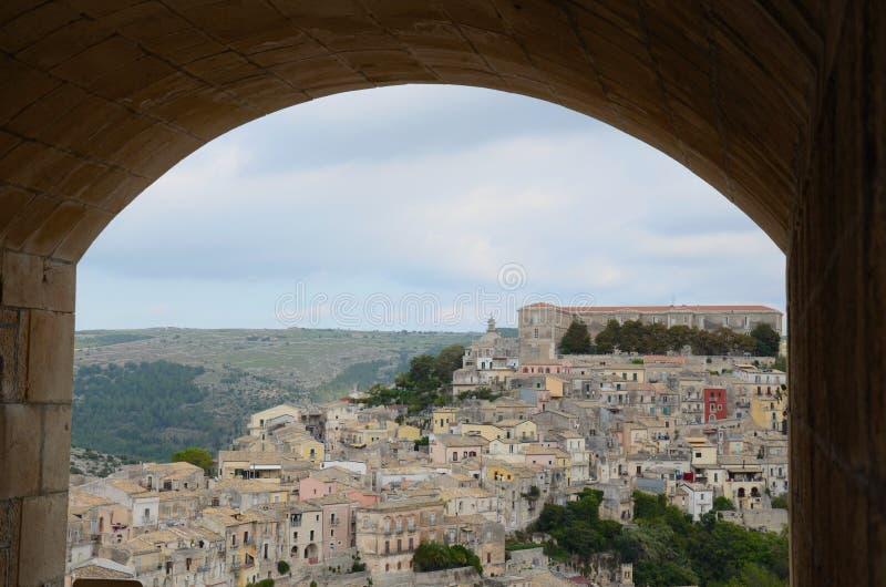 Mening op Ragusa in Sicilië door een boog stock foto's