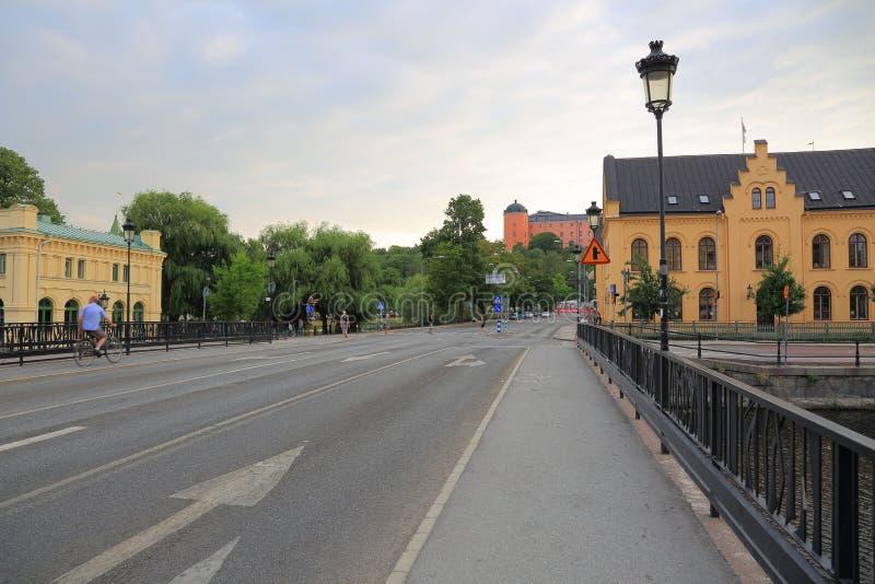 Mening over één van centrale straten in Uppsala, Zweden, Europa Kleine brug over rivier, gele gebouwen, rood kasteel ver weg royalty-vrije stock foto