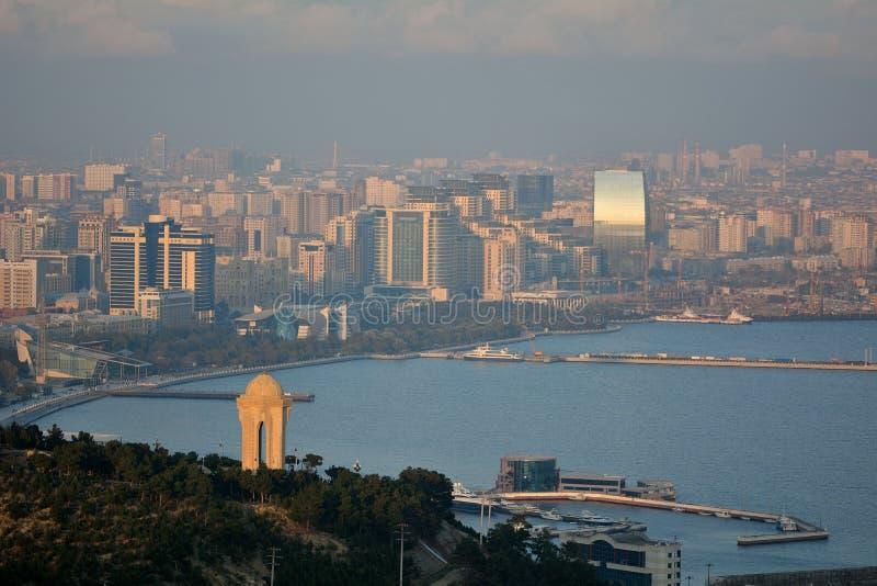 Mening over Baku en het Kaspische Overzees, in zonneschijn met nevel die het 20 Januari-monument in voorgrond tonen stock afbeeldingen
