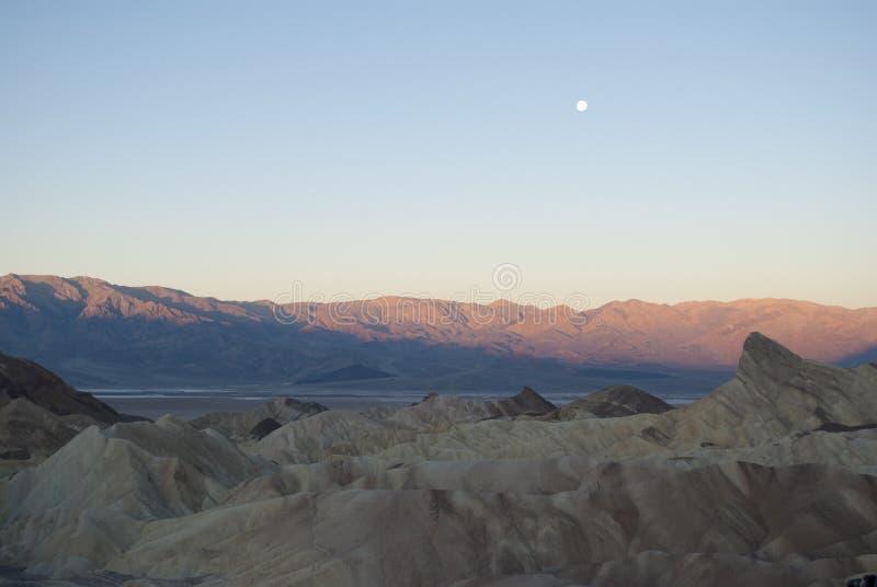 Mening over de bergen en de maan bij zonsopgang stock fotografie
