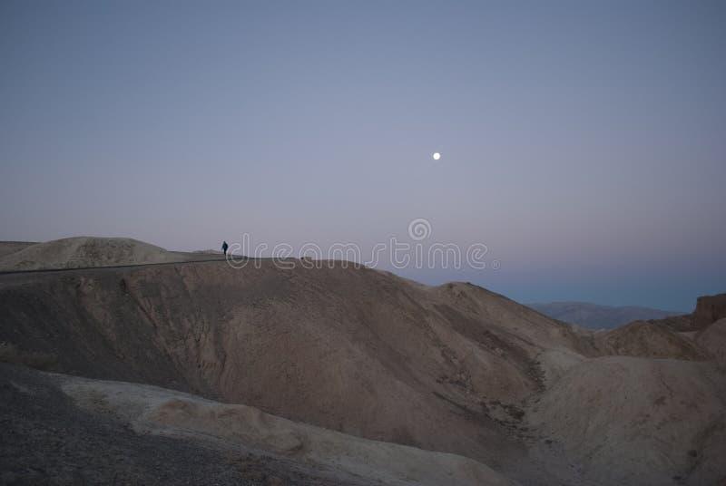 Mening over de bergen en de maan met een eenzaam menselijk figuur aangaande de berg vlak vóór zonsopgang stock fotografie