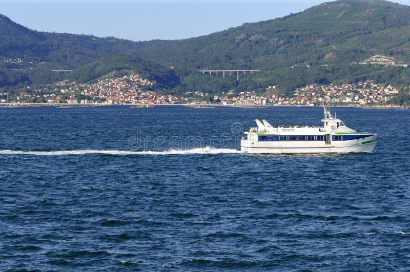 Mening over getijderivier met veerbootdorp en bergen stock afbeelding