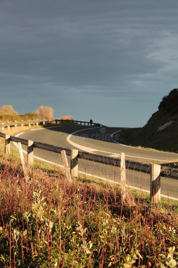 Mening over kromme van lege weg op richel van Atlantische kust in zonlicht en bewolkte hemel stock foto