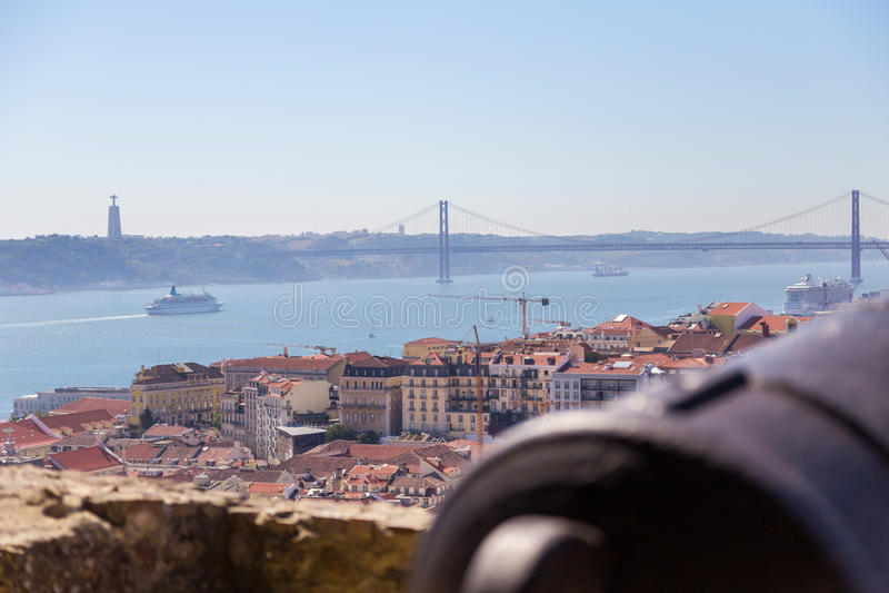 Mening over Lissabon met de oude boomstam van het metaalkanon stock foto