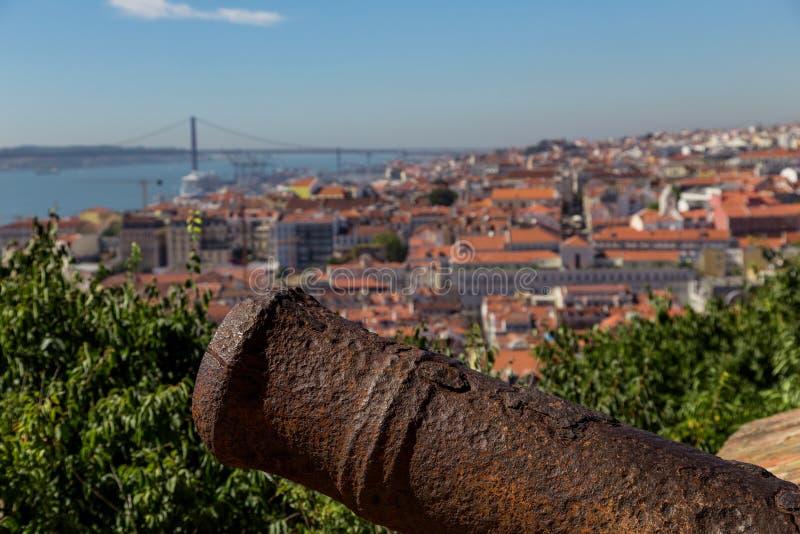 Mening over Lissabon met de oude boomstam van het metaalkanon stock afbeeldingen