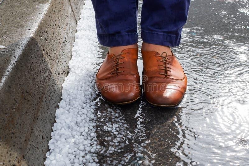 Mening over natte schoenen die zich dichtbij hagelstenen na hagelbui bevinden stock foto's