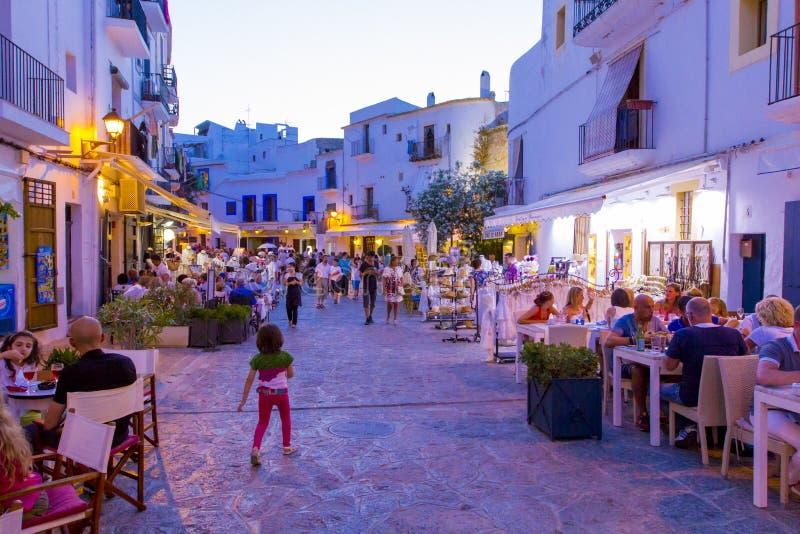 Mening over overvolle straat met koffie, bars en restaurants in oude stad Dalt Vila, in de zomer in avondverlichting, Ibiza, Span royalty-vrije stock afbeeldingen