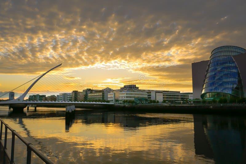 Mening over Rivier Liffey in Dublin bij Zonsondergang met Samuel Beckett Bridge en Overeenkomstcentrum stock afbeelding