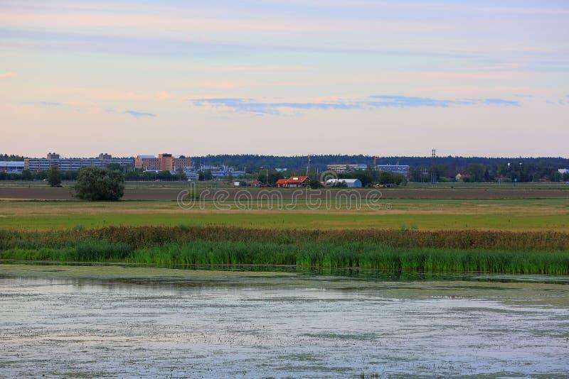 Mening over stad met grote gebouwen en plattelandshuisjes van rivierkant De tijd van de zonsondergang Groene aardkleuren en blauw royalty-vrije stock afbeelding