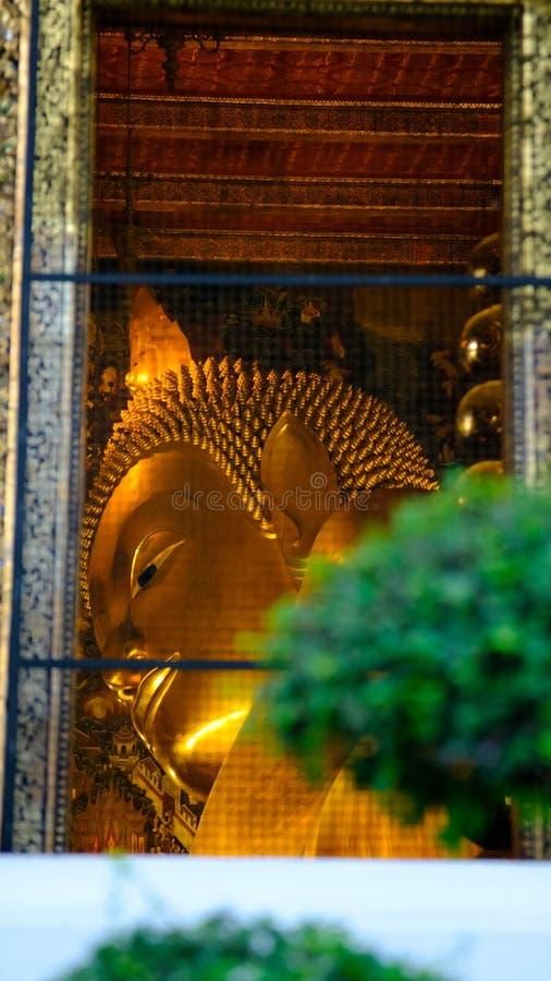 Mening over venster aan het Doen leunen van het gouden standbeeld van Boedha in zaal royalty-vrije stock fotografie