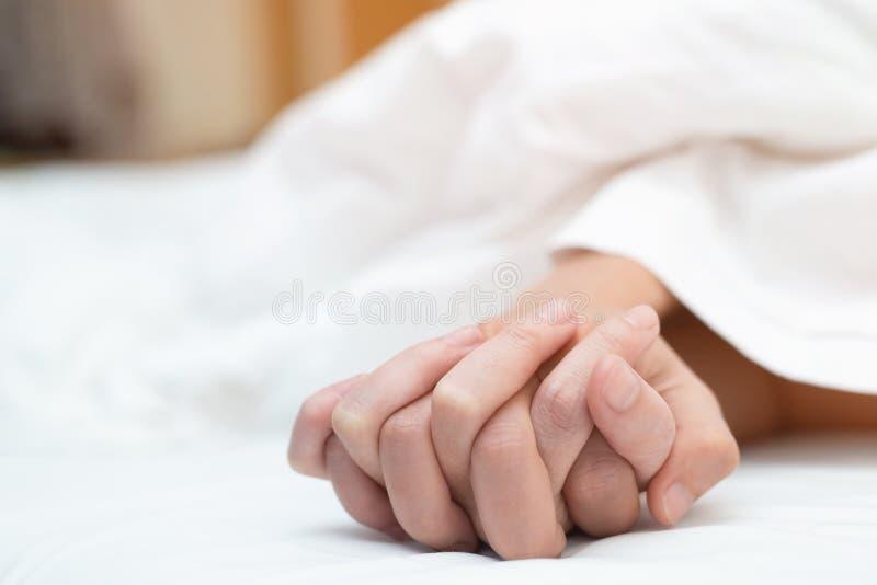 Mening på händer av passionpar som har att könsbestämma två vänpar som rymmer händer under vita ark för filt på sängen med lusta  arkivfoto
