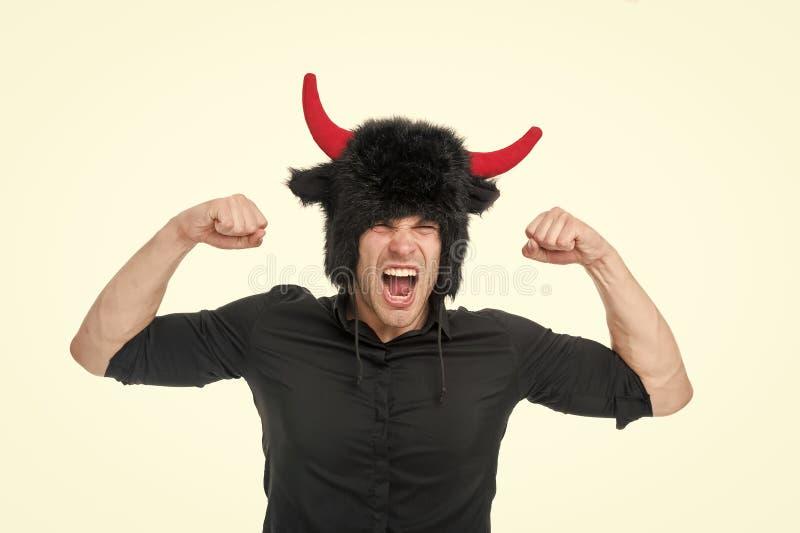 Mening så ilsket Mannen som ropar framsidan, bär hatten av jäkel med horn Aggressivt för svart skjorta för grabb visar ilsket sty royaltyfri fotografi
