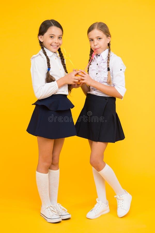 Mening sund är underbar Törstiga skolaflickor på gul bakgrund Små flickor som dricker fruktsaft från orange frukter royaltyfri fotografi
