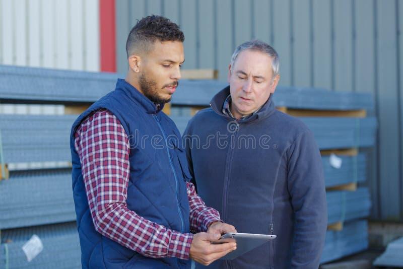 Mening twee arbeiders die buiten aan bouwwerf werken royalty-vrije stock foto