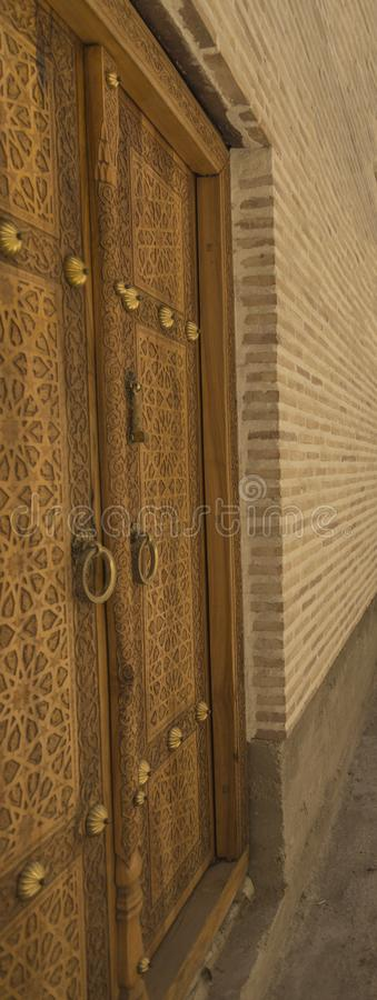 Mening van aan de linkerkant van oude overladen houten deur met mooie gravures in Boukhara, Oezbekistan stock foto
