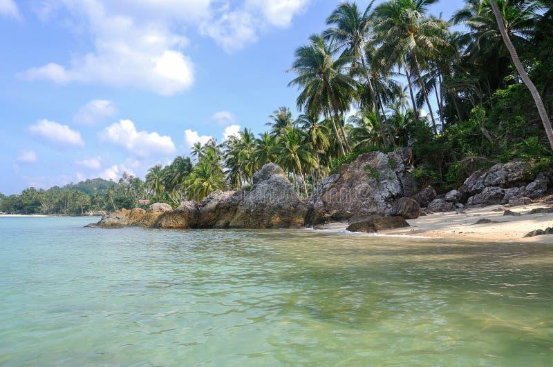 Mening van aardig tropisch strand met toneel rond stenen en palmen royalty-vrije stock afbeeldingen