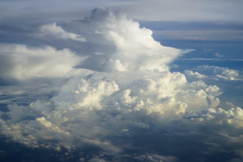 Mening van abstracte zachte pluizige witte wolk met schaduwen van blauwe hemel en aardeachtergrond van boven vliegend vliegtuigve royalty-vrije stock foto