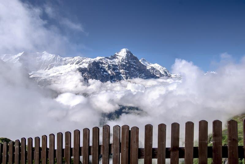 Mening van achter de omheining aan de Eiger-berg door wolken wordt omringd die stock foto's
