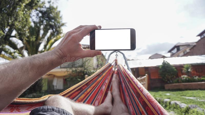 Mening van achter een jonge vrouw die in een hangmat liggen en smartphone bekijken royalty-vrije stock foto