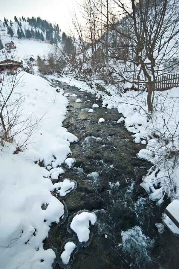 Mening van bevroren rivierplatteland Beek in sneeuwlandschap Roemeense kleine rivier in de winterlandschap, Roemenië, Moeciu Wild royalty-vrije stock foto