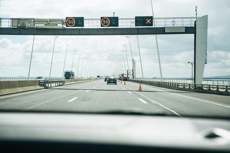 Mening van binnenuit de auto op een asfaltweg door de Vasco da Gamma-brug in Lissabon royalty-vrije stock afbeelding