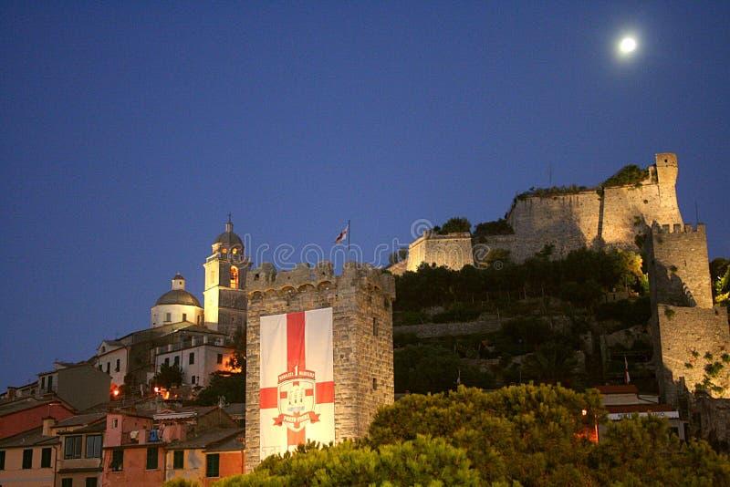 Mening van de gebouwen van Portovenere ` s bij nacht onder de maan met een een verlicht kasteel, toren en een kathedraal royalty-vrije stock afbeeldingen