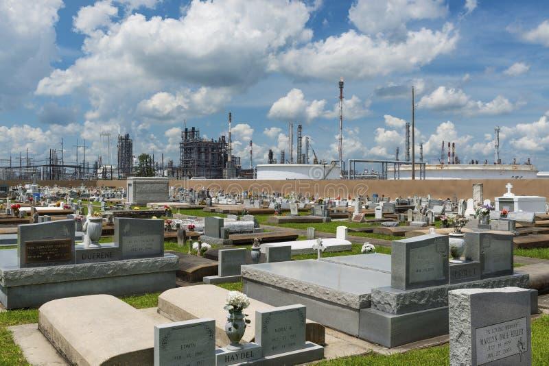 Mening van de Heilige Rozentuinbegraafplaats in Taft, Louisiane, met een petrochemische installatie op de achtergrond stock fotografie