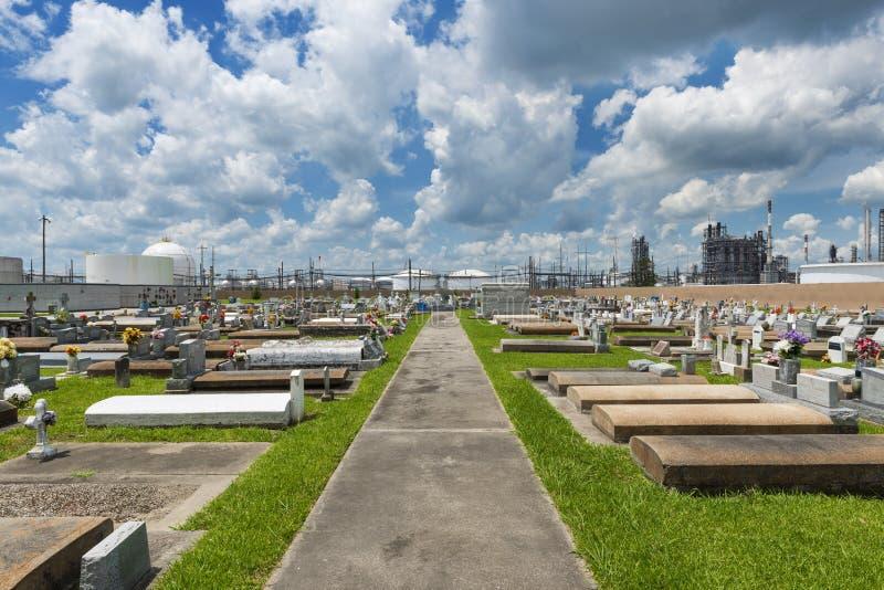 Mening van de Heilige Rozentuinbegraafplaats in Taft, Louisiane, met een petrochemische installatie op de achtergrond stock foto's