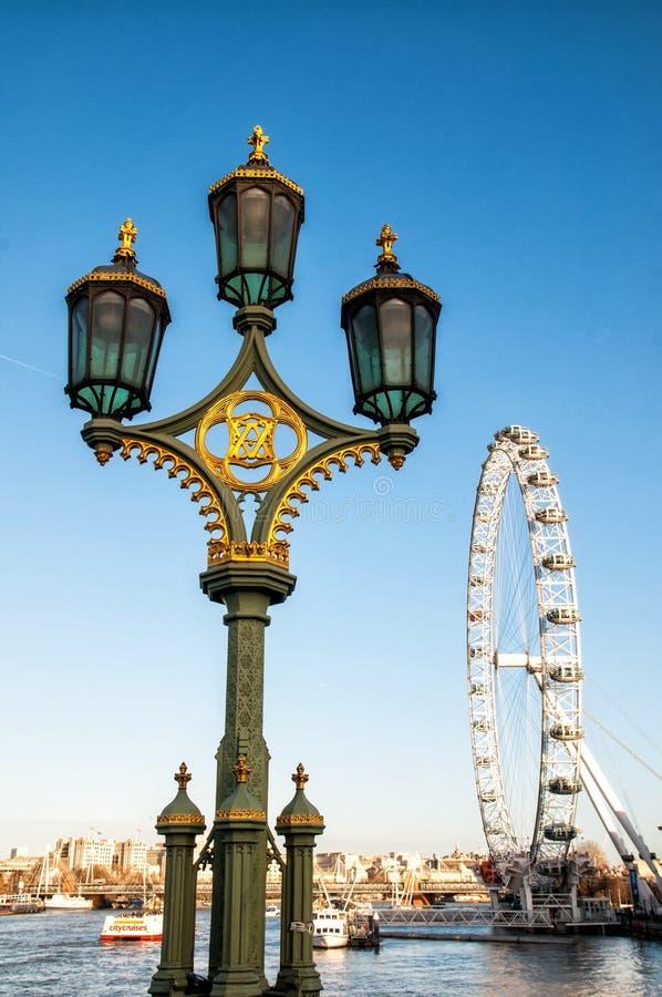 Mening van de het Oog en straatlantaarn van Londen op de brug van Westminster in Londen stock afbeelding