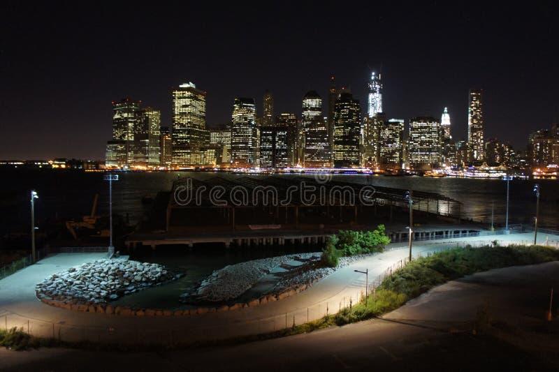 Mening van de horizon van Manhattan bij nacht uit Brookyln-Hoogten wordt gevergd die stock afbeeldingen