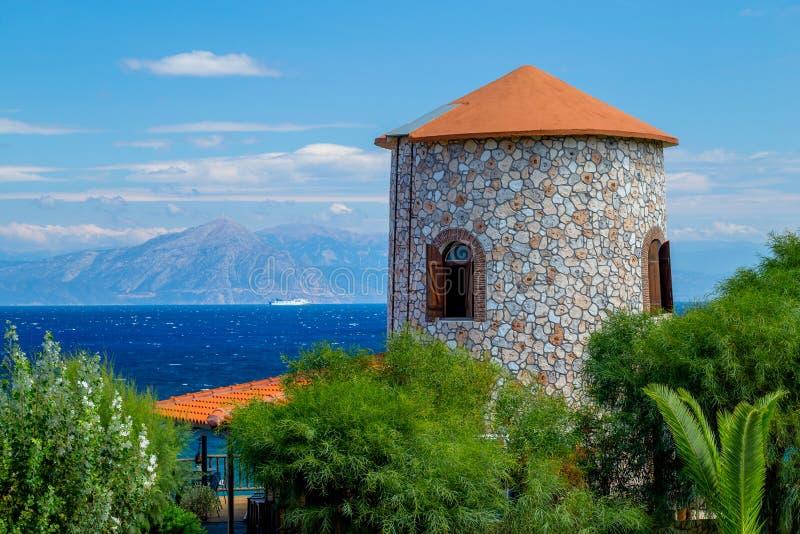 Mening van de Oude Griekse Windmolentoren en het Overzees met Schip en Verre Kustlijn royalty-vrije stock fotografie