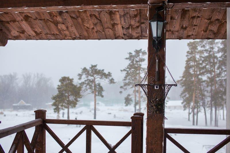 Mening van de portiek aan de straat van een buitenhuis op een de winter sneeuwdag vóór het Nieuwjaar stock fotografie