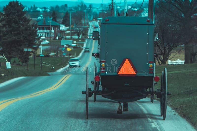 Mening van de rug van ouderwets, Amish met fouten met een paardrijden op grint landelijke weg stock foto's