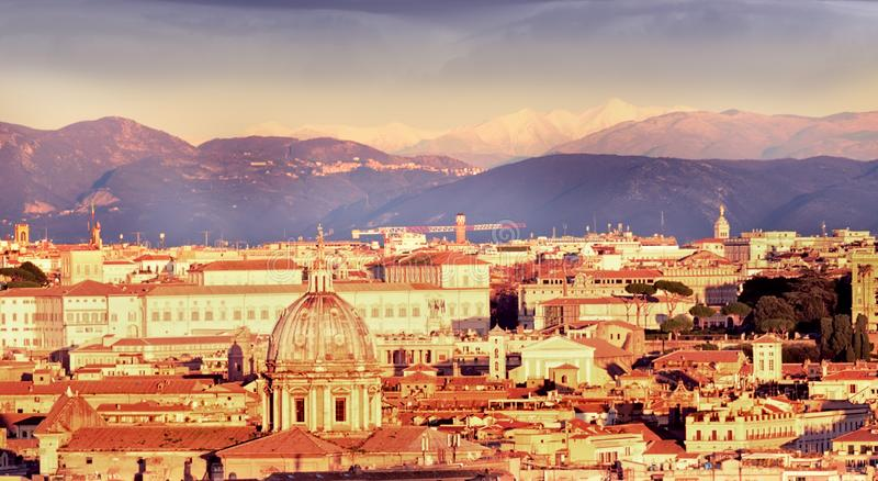 Mening van de stad bij zonsondergang Op de horizonbovenkanten van bergen in de sneeuw rome stock foto's