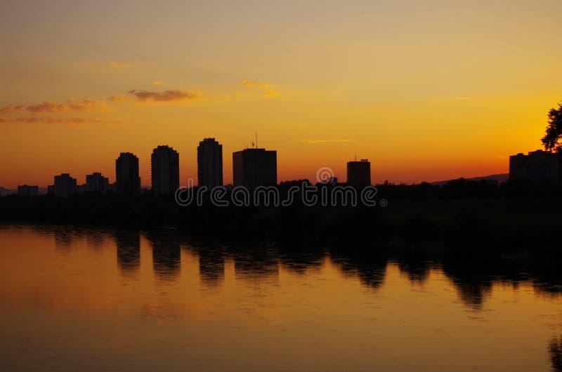Mening van de stad over de rivier in de avond. stock afbeelding
