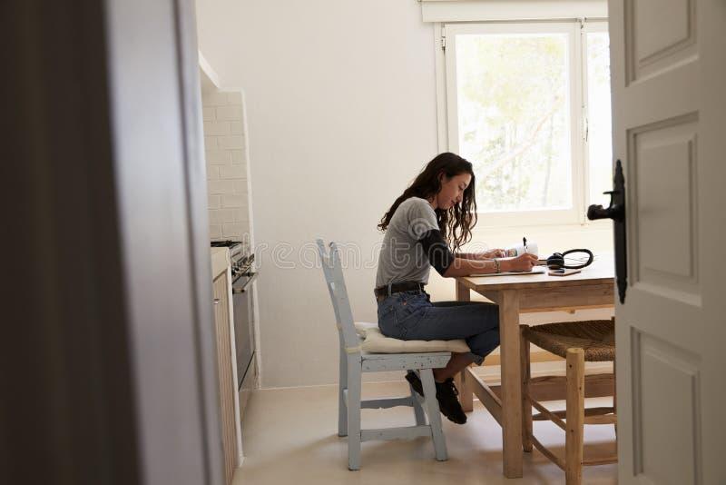 Mening van deuropening die van tiener thuiswerk in keuken doen stock foto's