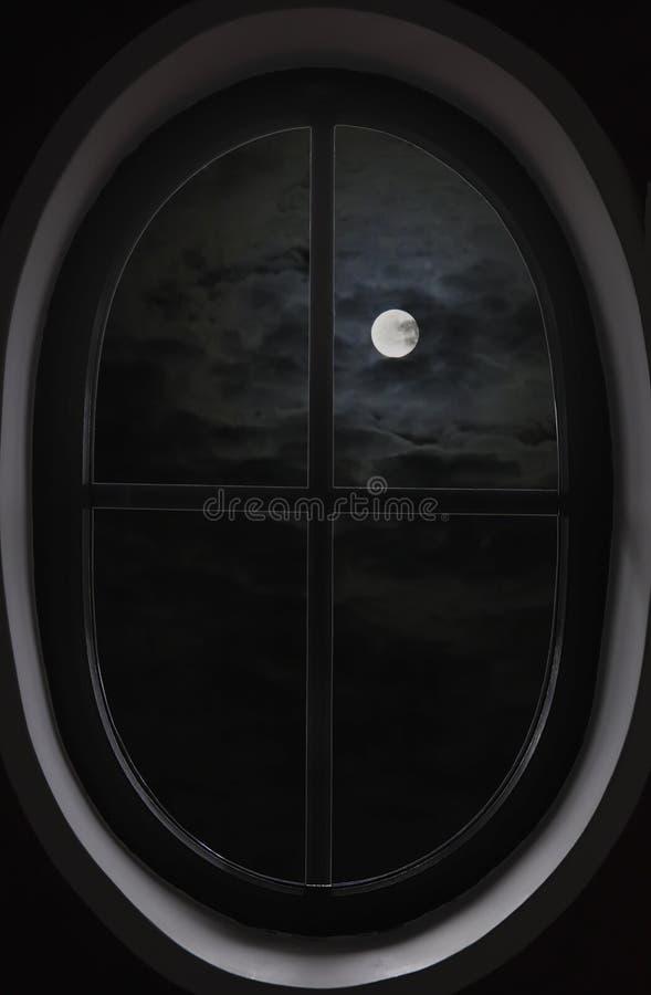 mening van donkere wolken, volle maan door het ovale venster stock afbeelding