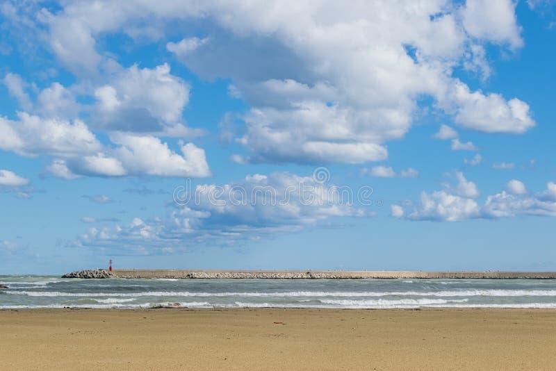 Mening van een de winterstrand met hemel en witte wolken stock afbeeldingen