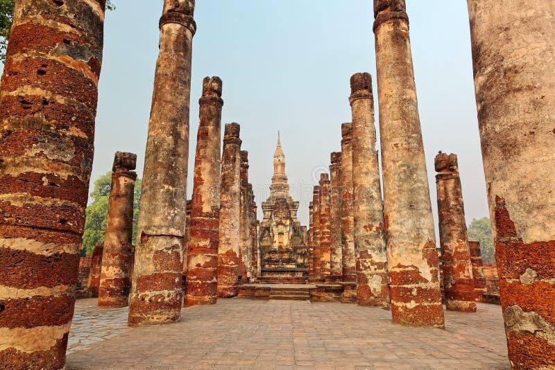 Mening van een gezet standbeeld van Boedha onder geruïneerde kolommen in Wat Mahathat, een oude Boeddhistische tempel in het Hist royalty-vrije stock afbeeldingen