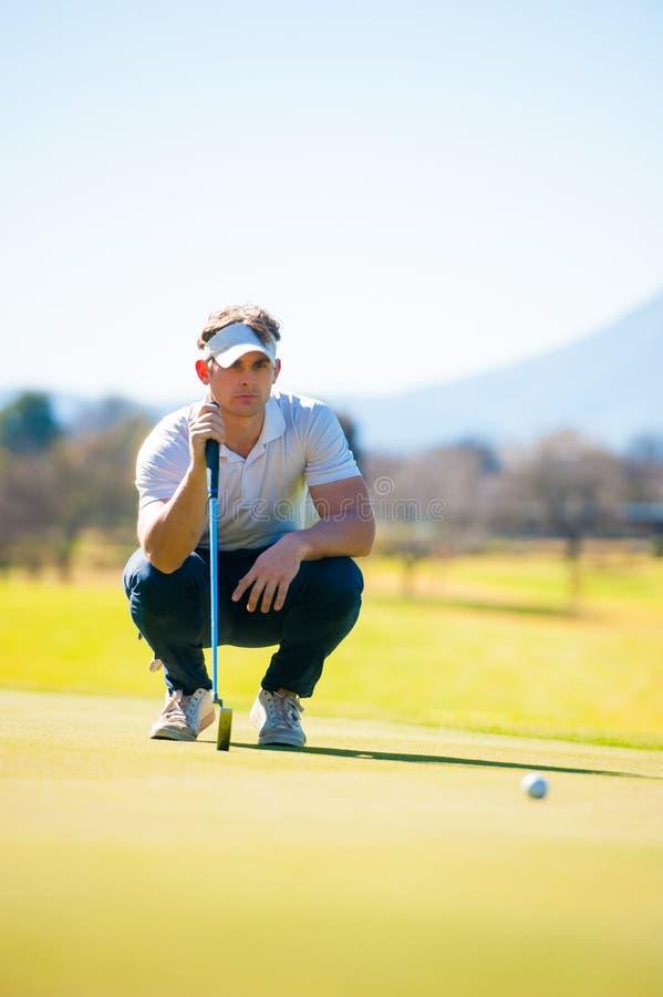 Mening van een golfspeler die zijn schot plannen aan de speld stock afbeelding